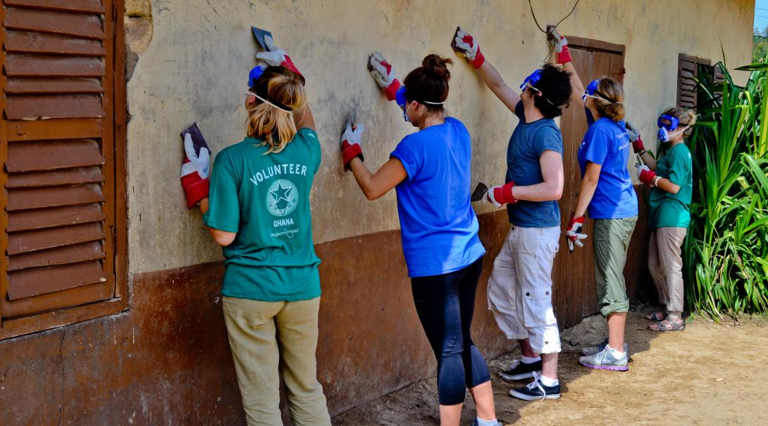 Construction volunteers in Ghana scraping off old paint from a wall.